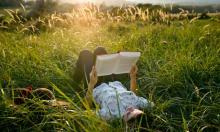 Student lying in grass reading